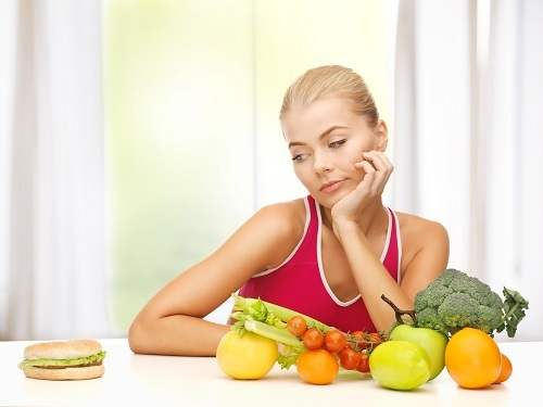 picture of doubting woman with fruits and hamburger